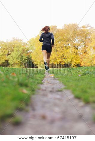 Fit And Healthy Female Athlete Running In Park