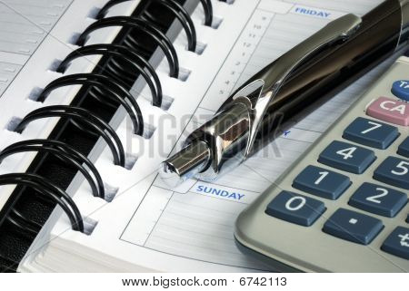 Close up view of the calculator, pen, and the diary