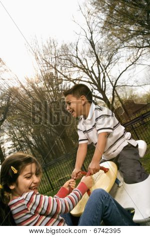Young Girl And Boy Playing On Seesaw
