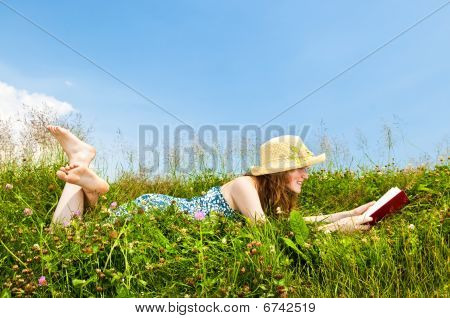 Young Girl Reading Book In Meadow