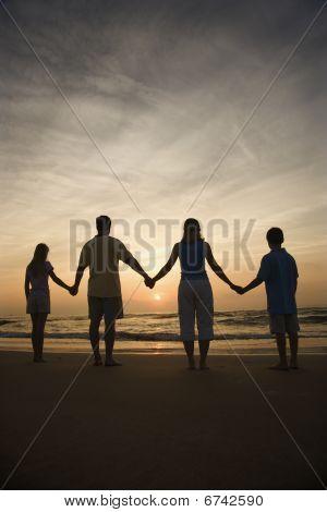 Familia cogidos de la mano en la playa