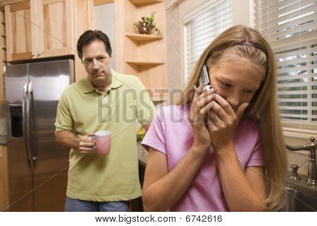 Hija de padre viendo en teléfono