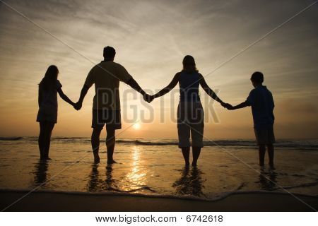 Family Holding Hands On Beach Watching The Sunset