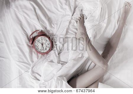 Sexy Female Legs With Clock On Bed In Bedroom