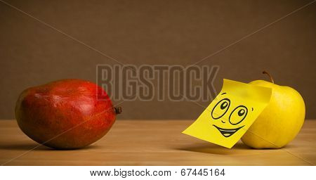 Apple with sticky post-it note reacting to mango