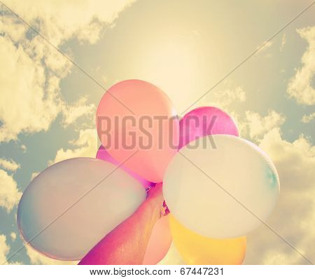 a person holding multi colored balloons done with a retro vintage instagram filter