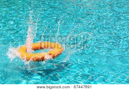 Orange Life Buoy And Splashing Water In Clear Swimming Pool