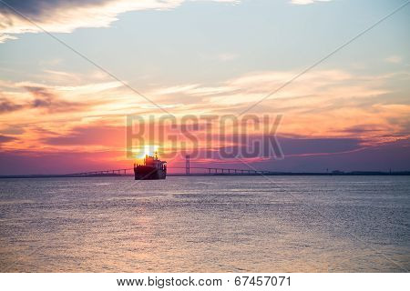 Frieghter Sailing Into Sunset At Bridge