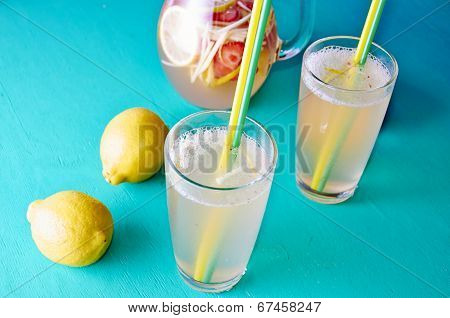 Cold summer dring - lemonade in pitcher with lemons around it