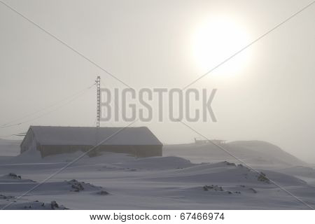Emergency Antarctic Station In The Fog In Front Of The Setting Sun