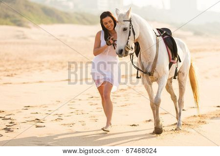 cheerful young woman walking with a horse on beach in early morning