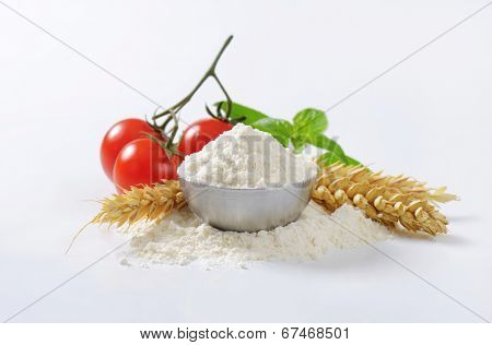 side view of bowl with flour, fresh tomatoes and wheat ears