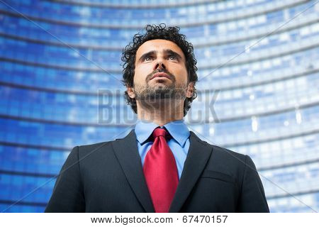 Portrait of a businessman in front of a glass palace