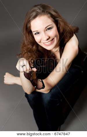ppy smiling caucasian girl with sunglasses sitting on suitcase