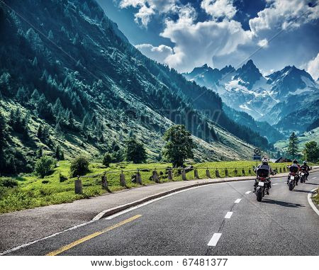 Motorcyclists on mountainous road, enjoying tour along Alps, summertime activities, wonderful mountain landscape, extreme vacation concept