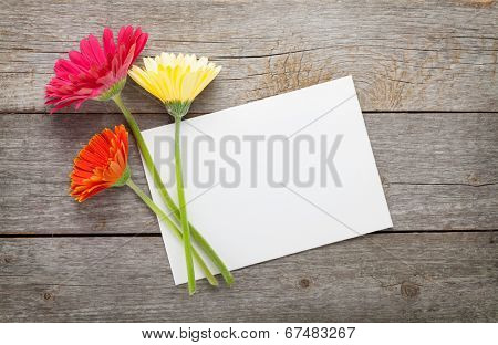 Three colorful gerbera flowers and blank greeting card on wooden table