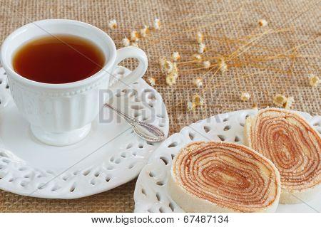 Bolo De Rolo (swiss Roll, Roll Cake) Brazilian Dessert On White Plate Cup Tea