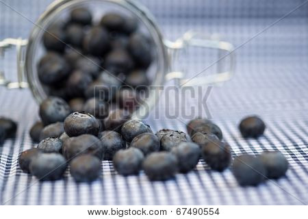 Fresh Blueberries Falling Out Of Glass Jar