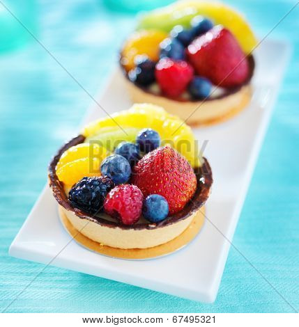 tart aux fruits desserts on a plate with blue table cloth