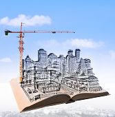 stock photo of land development  - sketching of building construction on flying book over urban scene use for civil engineering and land development topic - JPG