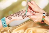 stock photo of mehndi  - Process of applying Mehndi on female hand - JPG