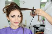 stock photo of apron  - Young woman hairdresser do hairstyle girl in beauty salon - JPG