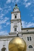 stock photo of dom  - Sculpture of a man on a golden sphere on the Kapitelplatz next to the Salzburger Dom in Salzburg Austria - JPG