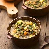 foto of legume  - Vegetarian soup made of lentils spinach potato carrot and onion served in dark brown bowls  - JPG