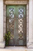 stock photo of burial-vault  - Front view of weathered mausoleum door with green vegetation at the bottom - JPG
