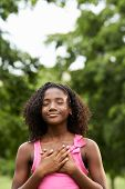 stock photo of daydreaming  - Ecology and environment-Portrait of young african american girl touching her heart in park smiling and daydreaming with eye closed