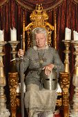 stock photo of throne  - Mature pensive medieval knight on the throne - JPG