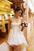 picture of clevage  - Beautiful young bride with a short gown and a bouquet in ger hand looking down - JPG