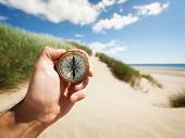 image of deserted island  - Hand holding a compass on the beach by sea concept for guidance - JPG
