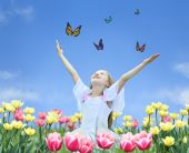 stock photo of young girls  - little girl in tulips with hands up and butterfly collage - JPG