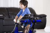 image of physically handicapped  - Disabled child in standing up in his walker - JPG