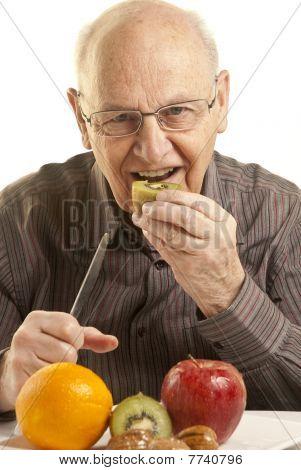 Senior Man Eating Fresh Fruit Over White Background