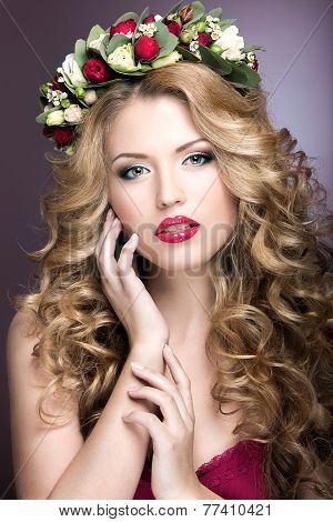 Portrait of a beautiful blond girl with curls and wreath of purple flowers on her head. Beauty face.