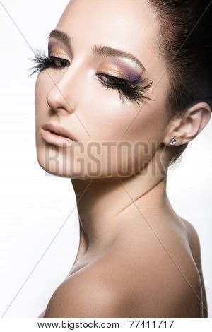 Girl with perfect skin and unusual makeup with feathers. Beauty face.