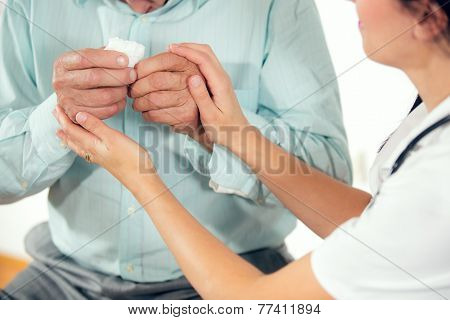 Female doctor holding senior patients hands at medical office