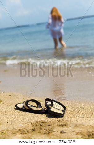Zapatillas de playa de arena y de la niña en el océano fuera de foco