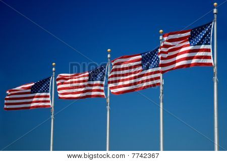 Banderas de Estados Unidos aleteo en el viento, el monumento a Washington