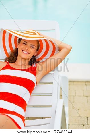 Portrait Of Smiling Young Woman In Hat Sitting Laying On Chaise-longue