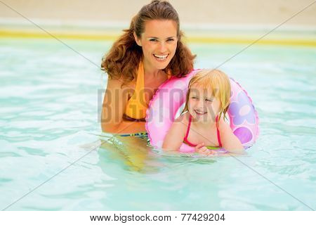 Portrait Of Happy Mother And Baby Girl With Swim Ring Swimming I