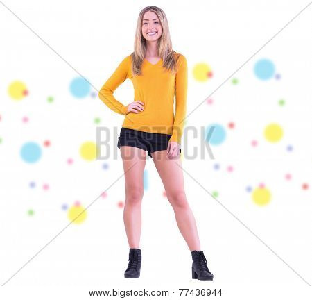 Stylish blonde smiling at camera against dot pattern