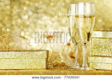 Two elegant flutes of sparkling champagne with decorative golden gifts