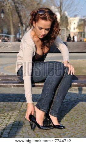Young Woman Putting On Shoes In Street