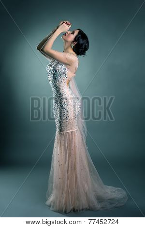 Pretty model posing in wedding dress with crystals