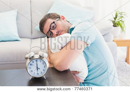 Bored man on the table beside alarm clock hugging a pillow at home in the living room