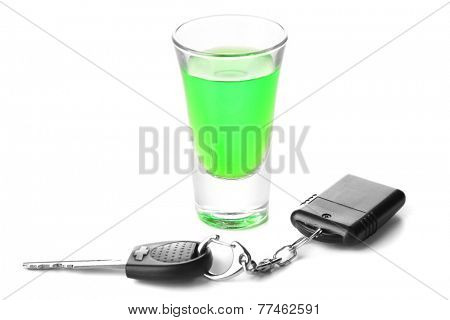 Glass of alcoholic drink and car key, isolated on white