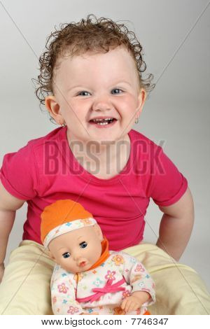 Happy baby girl with her doll on grey background